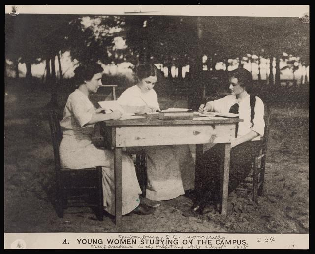 Young Women Studying on the Campus, 1918, Photomechanical print shows three young women studying outdoors at a desk. Library of Congress