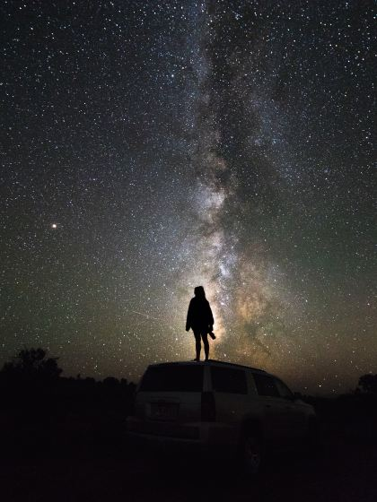 Photo by Logan Lambert on Unsplash; Person standing on car looking up at the night sky